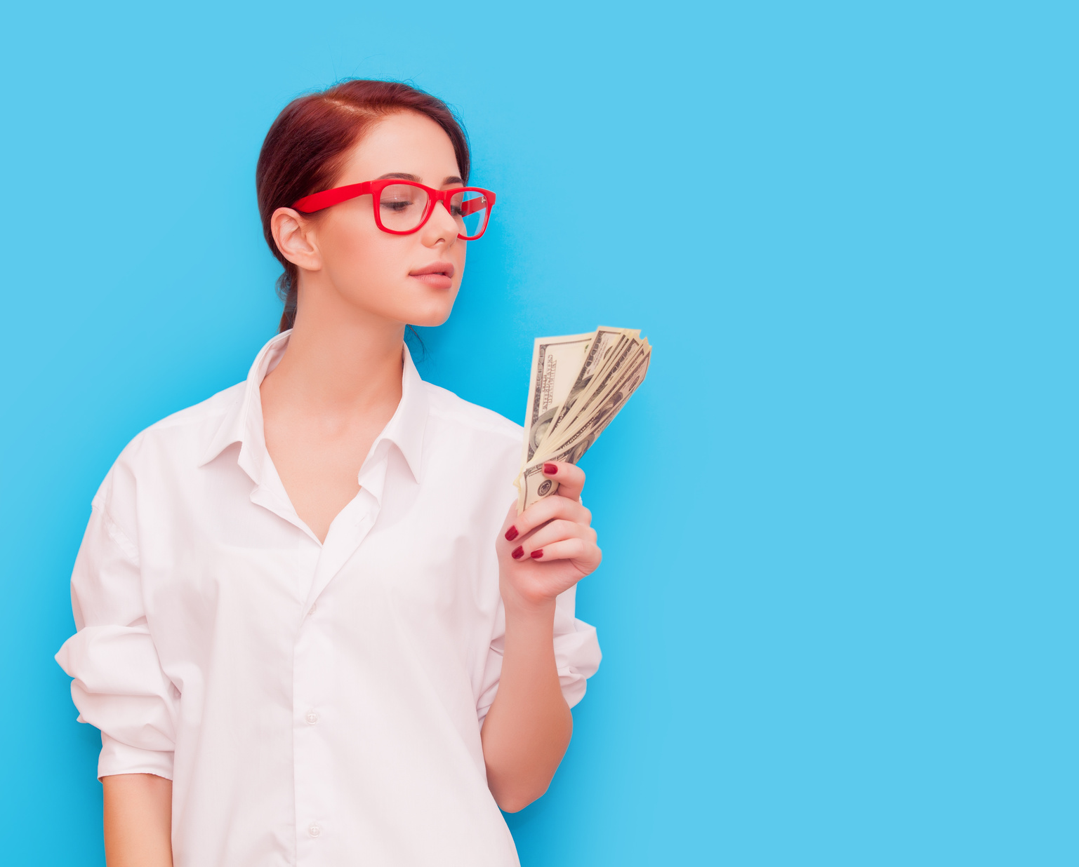 Portrait of redhead woman in red glasses with money on blue background