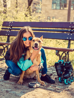 Smiling casual female with her brown pitbull dog in a park.