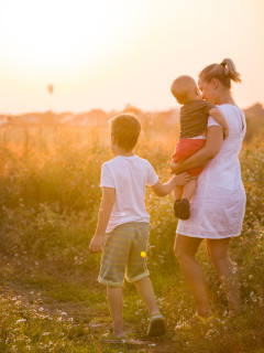 Beautiful young woman with two boys on the daisy meadow on a sunny day. Happy family on summer sunset. Kid boy giving flower to his mother. Mum with baby and kid.