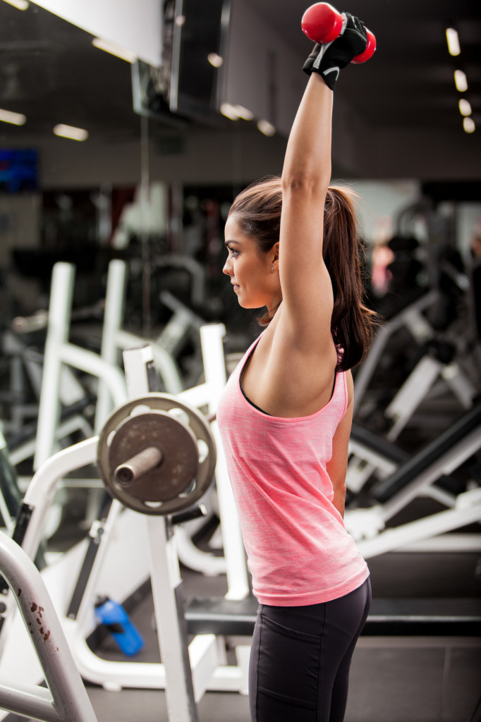Cute young woman lifting weights