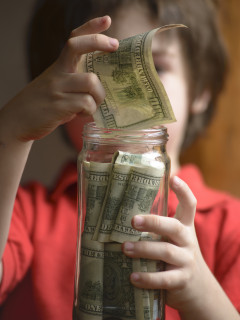 Child entering their savings in a jar