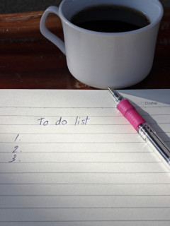 To do list  with a pen and cup of fresh coffee on wood background in morning