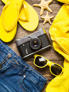 Summer women's accessories: yellow step-ins, denim shorts,  camera, sunglasses on  wood background.