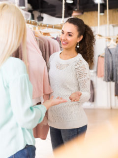 Two smiling young female friends choosing jersey at the apparel store