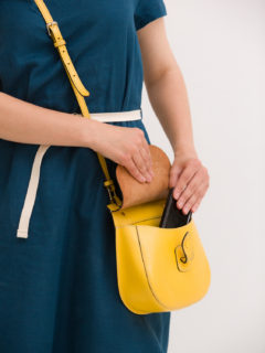 Closeup of woman's hands taking out smartphone from yellow purse. Image of young stylish woman taking cellphone out of handbag. Girl with phone. Communication and lifestyle concept