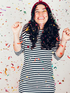 Laughing girl with striped dress and wool cap under a rain of confetti. Filter effect added. Filter effect added.